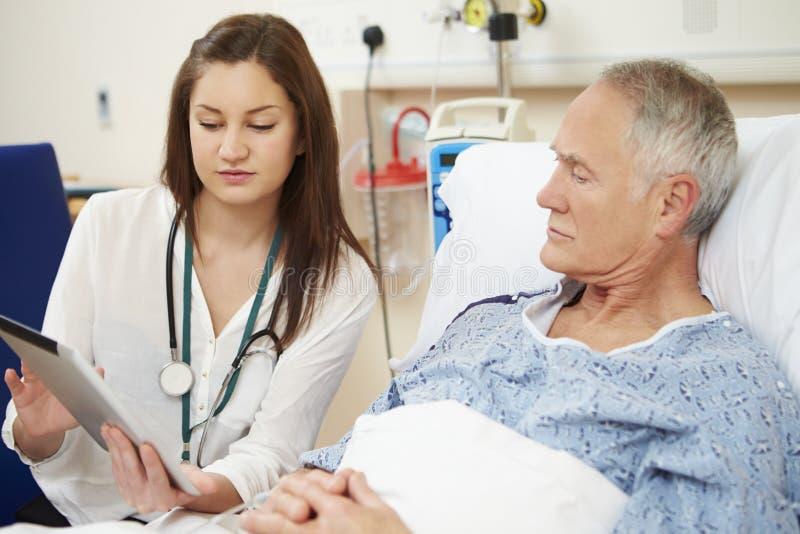A cama do paciente do doutor Sitting By Male usando a tabuleta de Digitas fotografia de stock royalty free