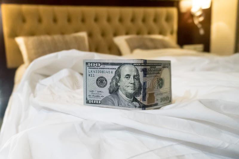 cama e dinheiro para simbolizar o custo do sexo foto de stock