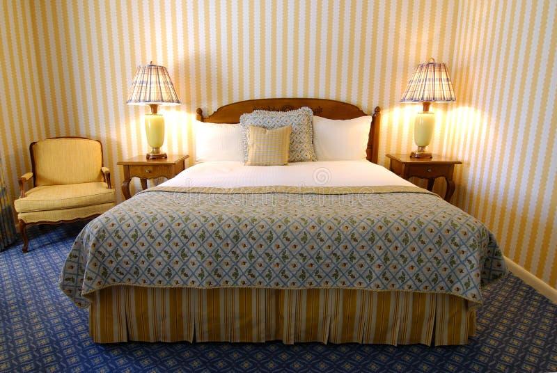 Cama en dormitorio foto de archivo