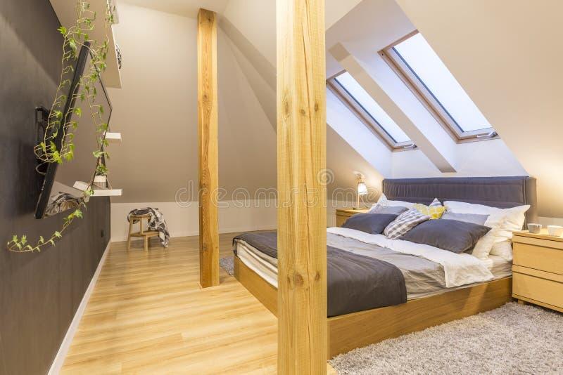 Cama en dormitorio de madera fotografía de archivo