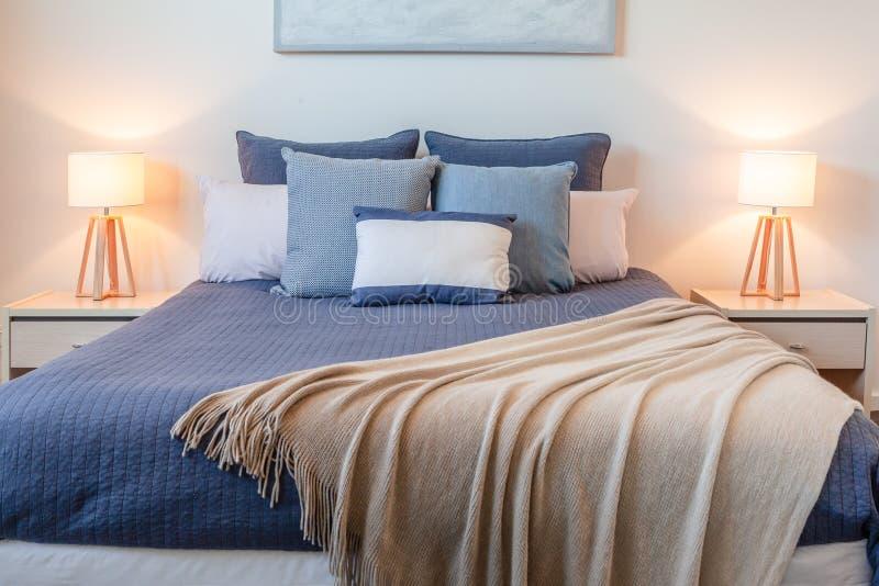Cama en un dormitorio con las lámparas de cabecera imágenes de archivo libres de regalías