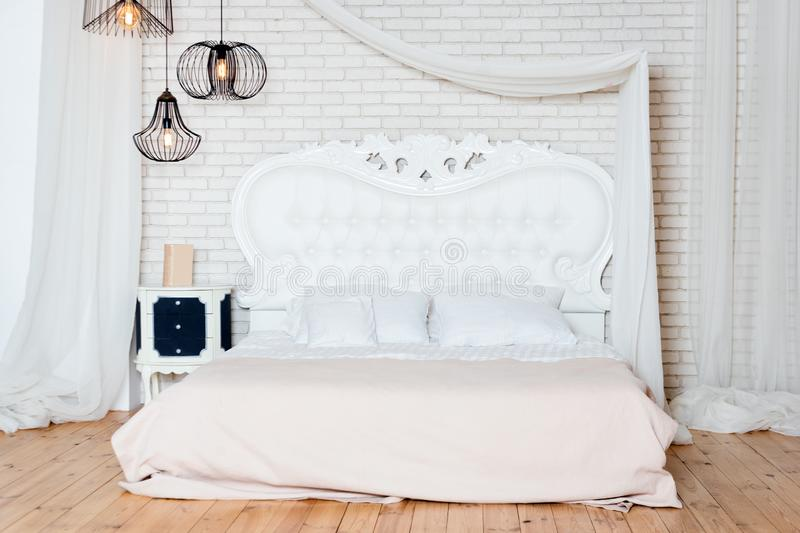 Cama enorme no apartamento do sótão Quarto do estilo do sótão com projeto branco fotos de stock