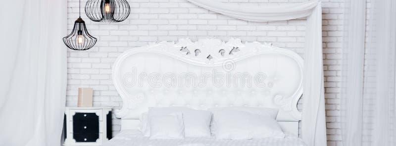Cama enorme no apartamento do sótão Quarto do estilo do sótão com projeto branco fotos de stock royalty free