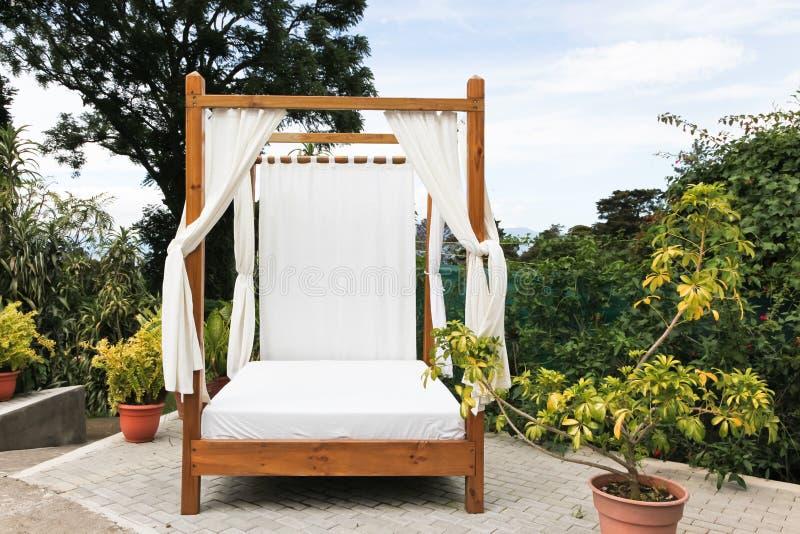 Cama exterior com cortinas fotografia de stock royalty free