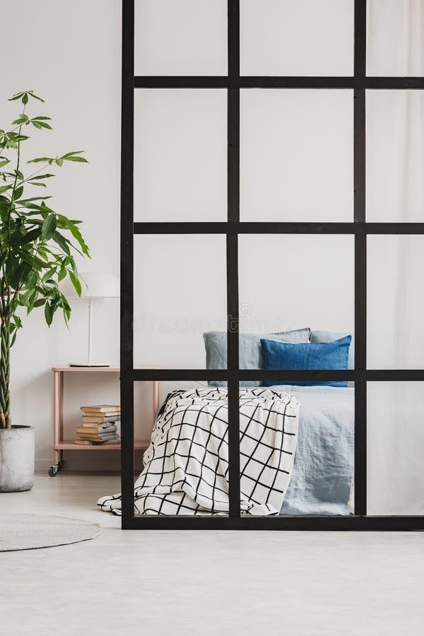 Cama gigante cómoda con lecho azul en el apartamento-estudio abierto brillante del plan con la división foto de archivo libre de regalías