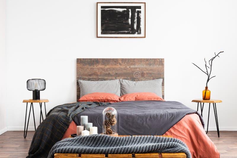 Cama gigante con lecho anaranjado y gris entre el nightstand de madera dos con la lámpara y el florero foto de archivo libre de regalías