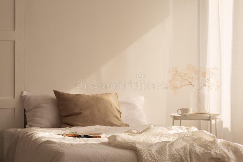 Cama gigante del ion de lino de las hojas en dormitorio mínimo con la pared vacía imagenes de archivo