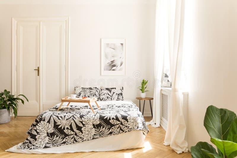Cama grande confortável com fundamento branco e preto do projeto da flor e uma bandeja do café da manhã sobre em um interior bril fotos de stock