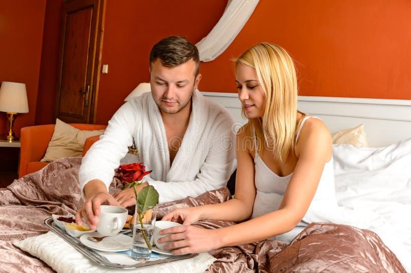Cama loving romântica dos pares da sala de hotel do pequeno almoço imagens de stock