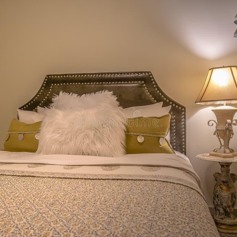 Cama matrimonial del cuadrado y tabla lateral redonda con la lámpara dentro de un dormitorio hermoso imágenes de archivo libres de regalías