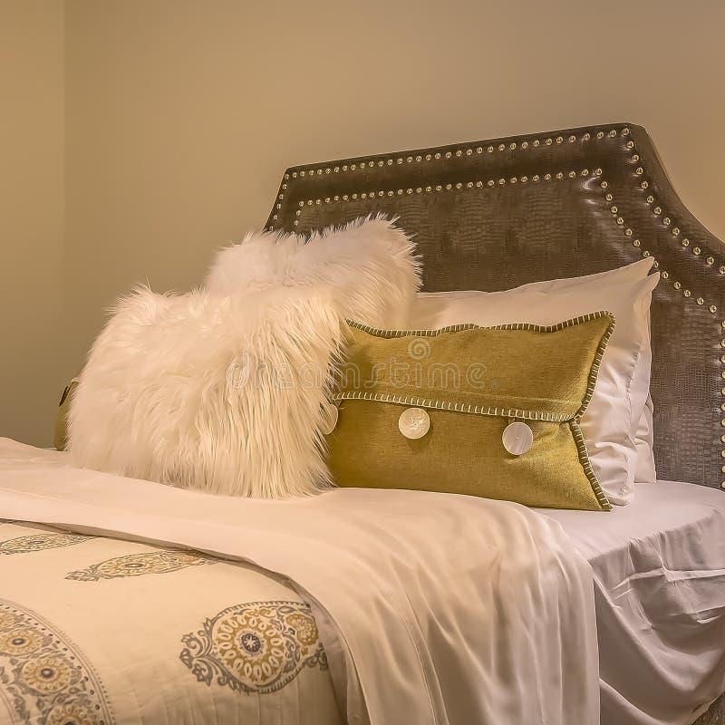 Cama matrimonial del marco cuadrado con las almohadas mullidas contra el cabecero tapizado del belgrave fotos de archivo