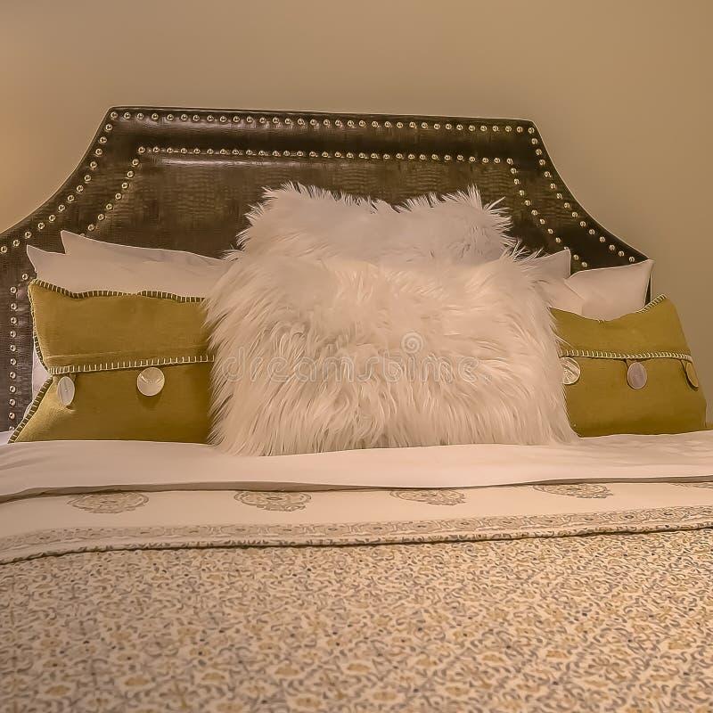 Cama matrimonial del marco cuadrado y tabla lateral redonda con la lámpara dentro de un dormitorio hermoso foto de archivo