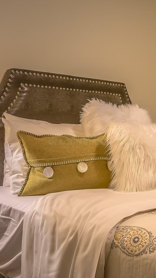 Cama matrimonial del marco vertical con las almohadas mullidas contra el cabecero tapizado del belgrave imagen de archivo libre de regalías