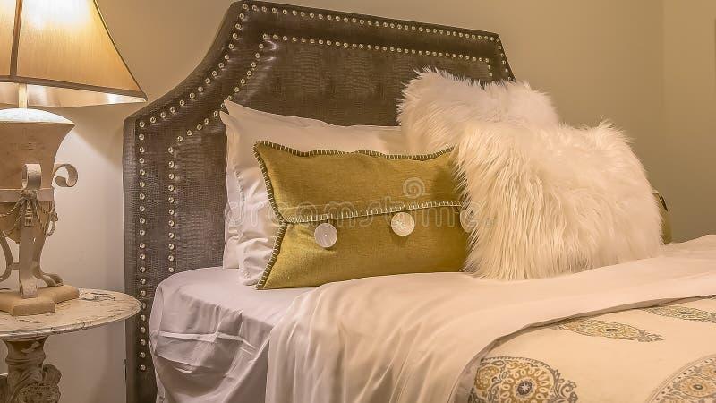 Cama matrimonial del panorama con las almohadas mullidas contra el cabecero tapizado del belgrave imagen de archivo