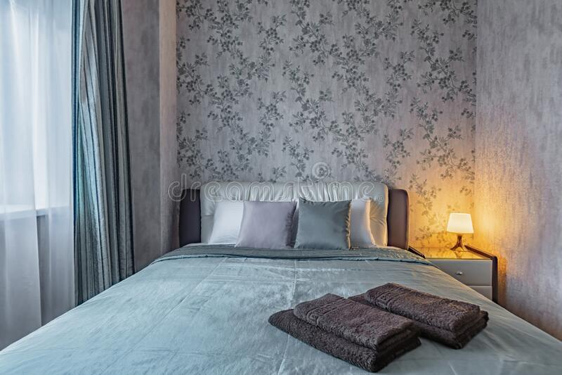 Cama mullida en un pequeño y acogedor dormitorio imagen de archivo