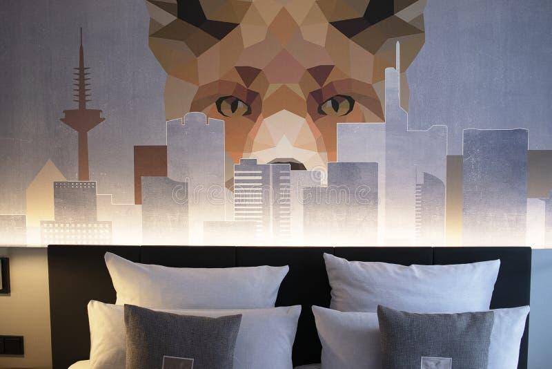 Cama no hotel com descansos, no desenho de parede da cidade e da raposa Descansos brancos na cama com uma parte traseira preta fotografia de stock