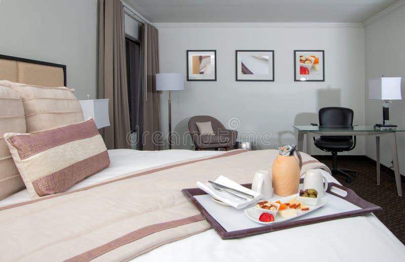Cama, sillas, y escritorio del suite de la mansión del hotel turístico fotos de archivo