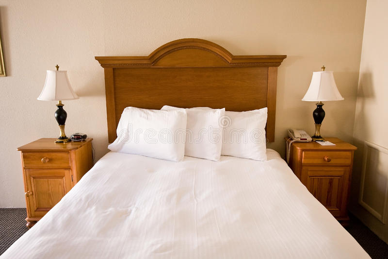 Cama simples, headboard, nightstands, lâmpadas fotografia de stock royalty free