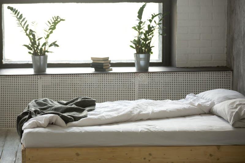 Cama sucia sin hacer en interior moderno del dormitorio con nadie fotografía de archivo