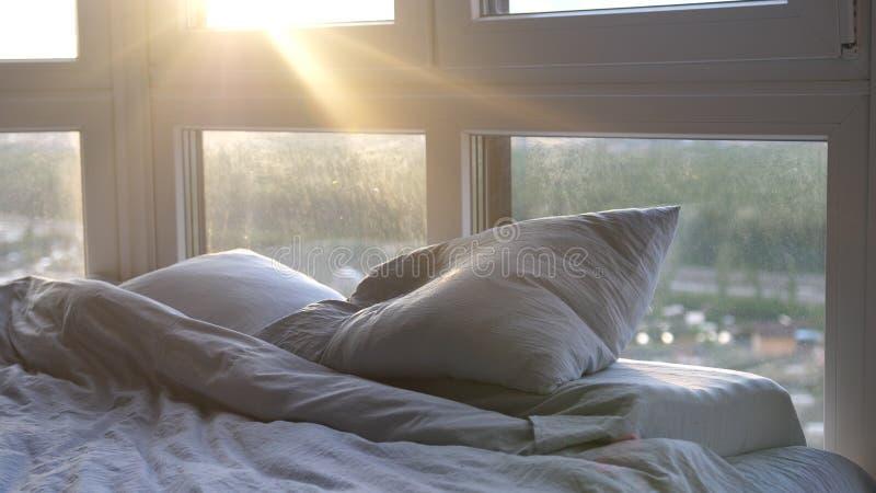 Cama vacía en la habitación moderna en la salida del sol Sun que brilla a través de la ventana con efectos de la llamarada de la  foto de archivo