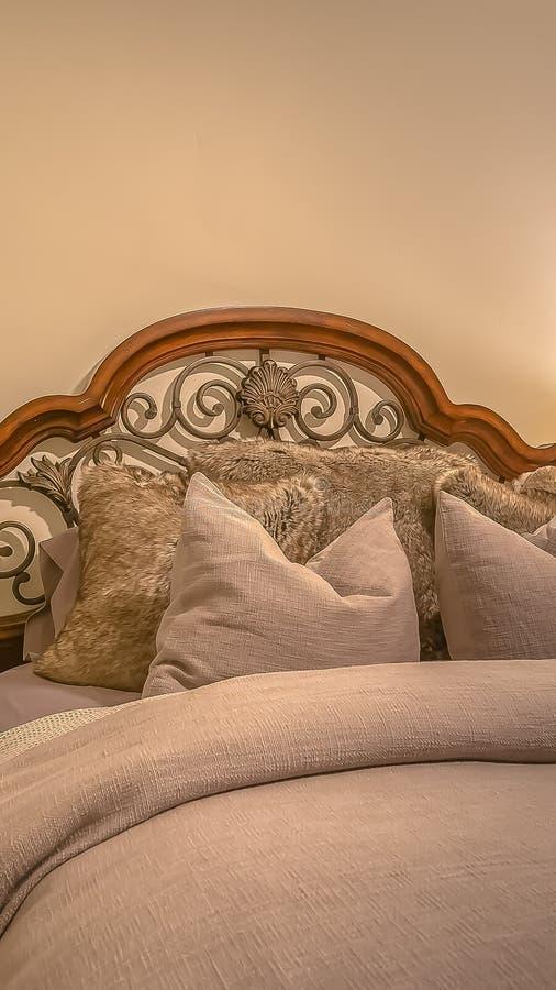 Cama vertical del marco con el cabecero de madera y del hierro labrado dentro del dormitorio de un hogar imagen de archivo