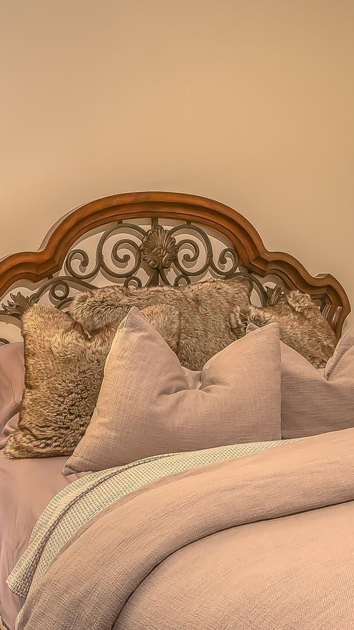 Cama vertical del marco con las almohadas mullidas contra el cabecero de madera y del hierro del worught fotografía de archivo libre de regalías