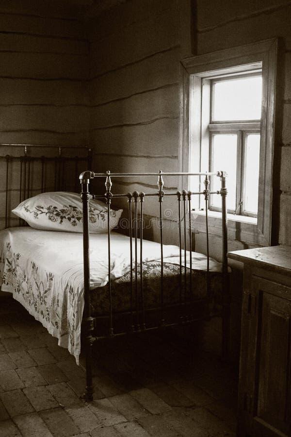 Cama vieja del hierro con una cama bordada blanca imagen de archivo