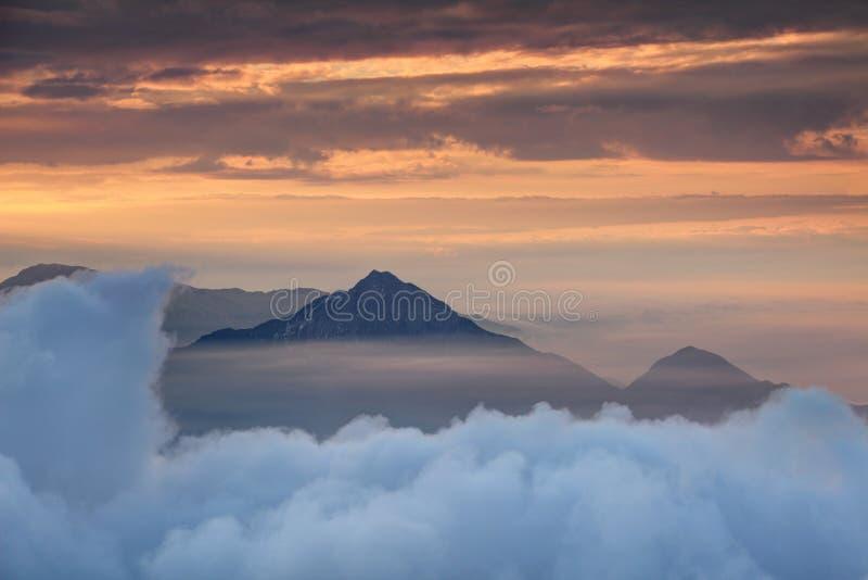 Camada densa da nuvem com pico cônico e névoa alaranjada da manhã imagem de stock