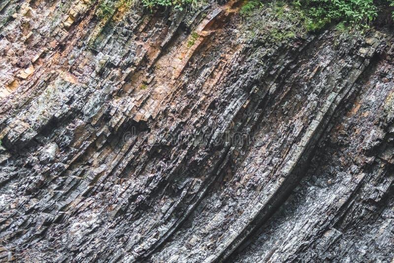 Camadas geological rochosas escuras multicamadas no banco de um rio da montanha Rocha com layers_ geological visível fotografia de stock