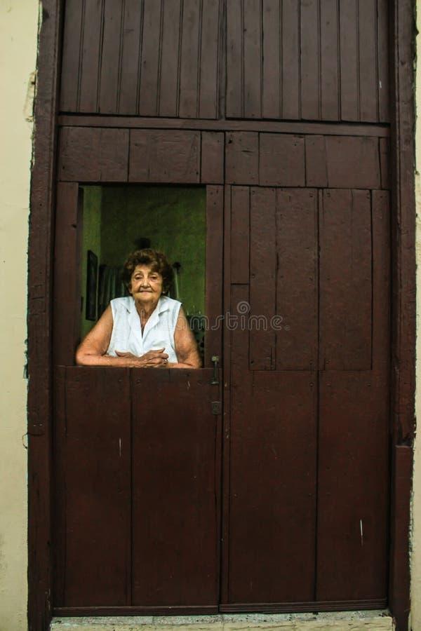 07/06/2015 Camaguey, Kuba: en gammal kvinna håller ögonen på tiredly ut ur fönstret av hennes vardagsrum shoppar i Kuba royaltyfria foton