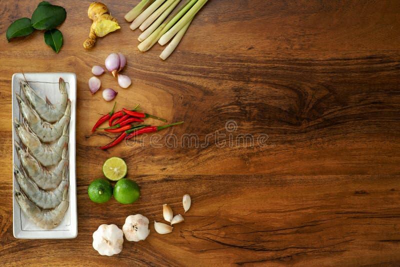 Camar?n crudo fresco en un plato blanco e ingredientes el cocinar para tom yum en el fondo de madera, visi?n superior foto de archivo libre de regalías