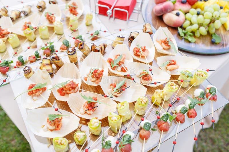Camarón delicioso y tomates cortados en un barco de madera El calabacín rueda con las nueces de pino Tabla de comida fría sabrosa fotos de archivo