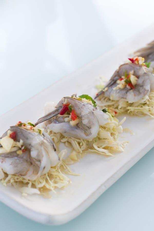 Camarón en salsa de pescados con la col cortada en el plato blanco en la tabla de cristal imagen de archivo libre de regalías