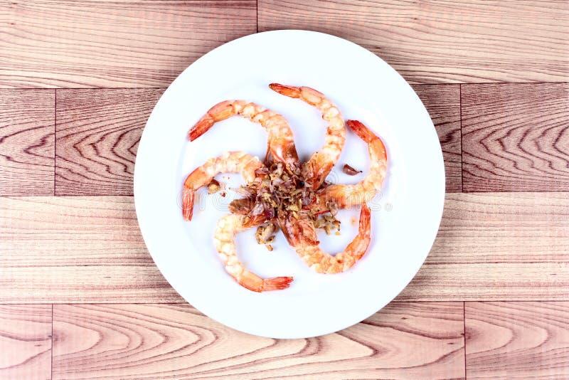 Camarón frito con ajo en el disco blanco fotografía de archivo