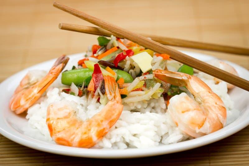 Camarões e arroz na placa com vegetais imagem de stock royalty free