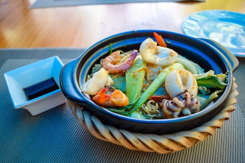 Camar?es e calamares fritados com macarronetes e os legumes frescos na bacia na tabela imagem de stock