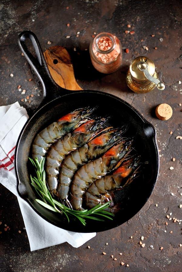 Camarões frescos crus do tigre com uma frigideira do ferro fundido com alecrins frescos e sal cor-de-rosa Alimento de mar saudáve imagem de stock royalty free