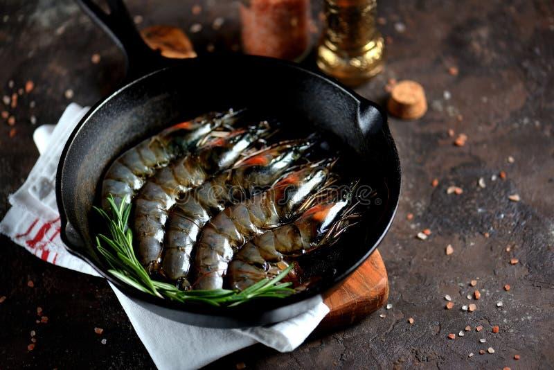 Camarões frescos crus do tigre com uma frigideira do ferro fundido com alecrins frescos e sal cor-de-rosa Alimento de mar saudáve imagem de stock