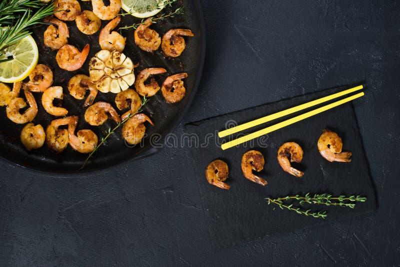Camarões fritados do rei em uma frigideira em um fundo preto com hashis amarelos fotos de stock