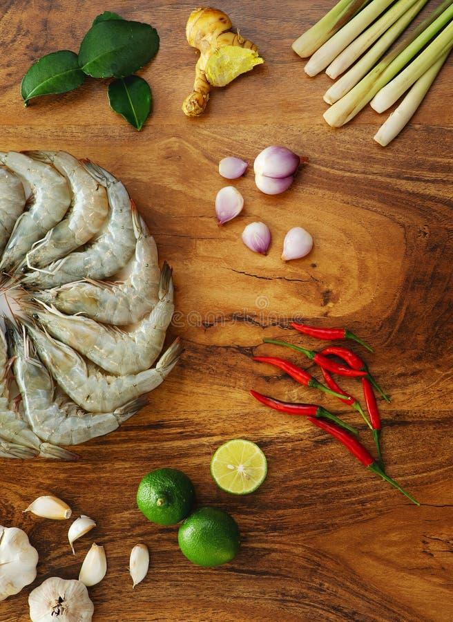 Camar?n crudo fresco en un plato blanco e ingredientes el cocinar para tom yum en el fondo de madera, visi?n superior foto de archivo