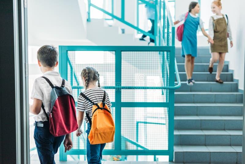 camarades de classe élémentaires d'âge descendant des escaliers image stock