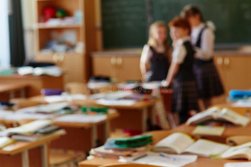 Camarades de classe dr?les Trois petits enfants mignons communiquer et discuter quelque chose position près du tableau noir Fond  photographie stock libre de droits