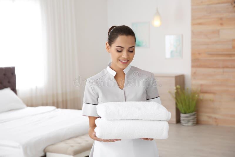 Camareira nova com toalhas limpas imagens de stock