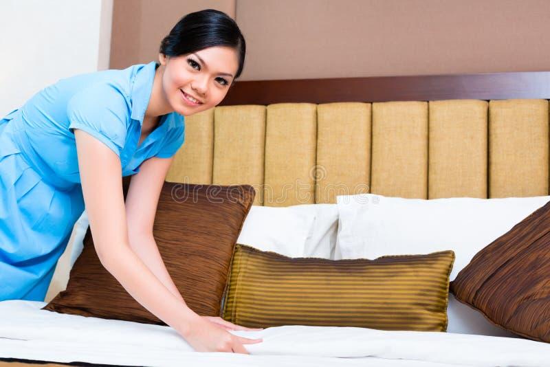 Camareira que faz a cama na sala de hotel asiática fotos de stock royalty free