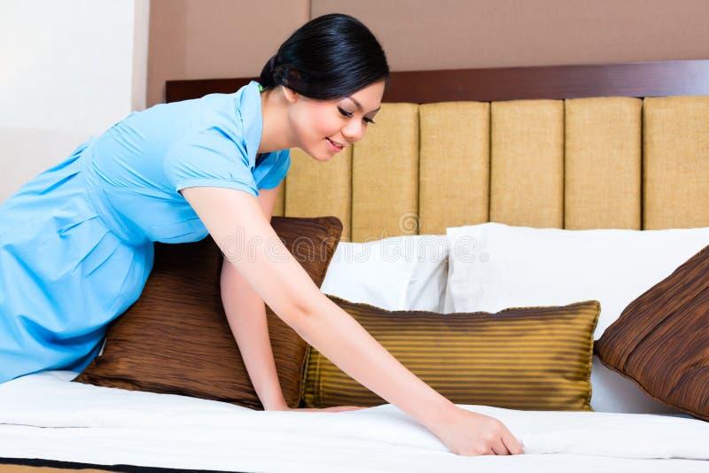 Camareira que faz a cama na sala de hotel asiática imagem de stock royalty free