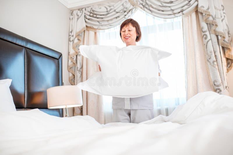 Camareira que faz uma cama no hotel foto de stock