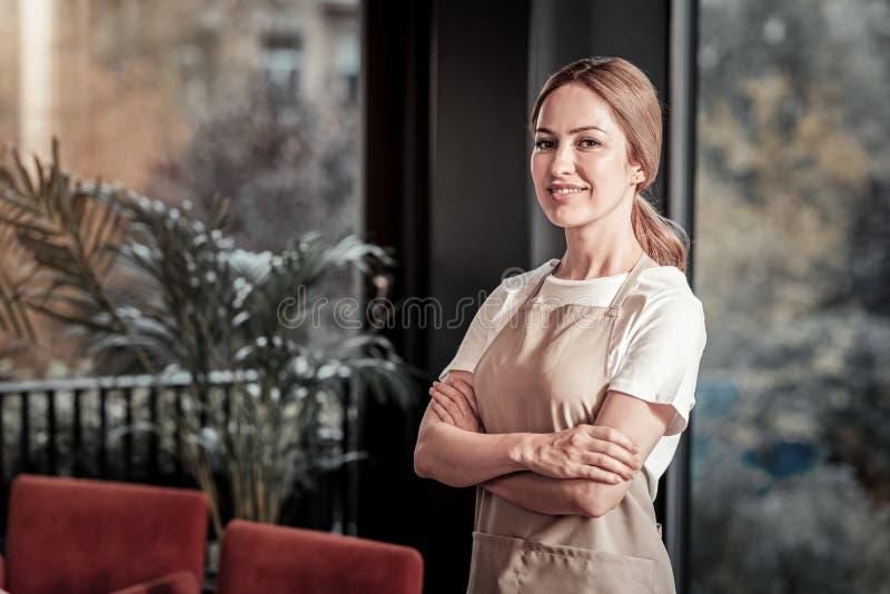 Camarera alegre elegante que parece satisfecha con su día laborable foto de archivo