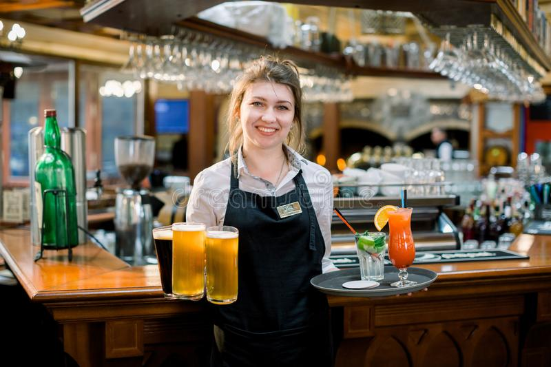 Camarera amistosa sonriente que sirve una pinta de cerveza de barril en un pub Retrato de la cerveza de servicio feliz de la muje imagen de archivo libre de regalías