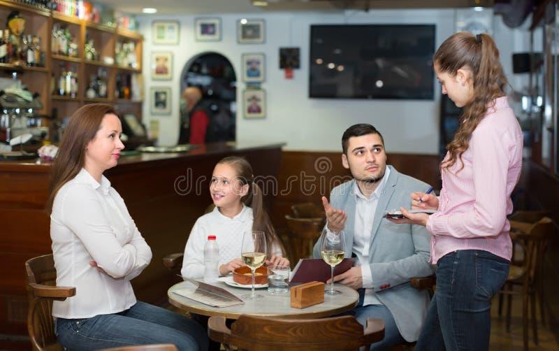 Camarera cansada y familia descontentada foto de archivo