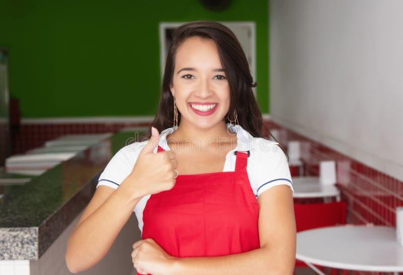 Camarera caucásica en un restaurante de los alimentos de preparación rápida que muestra el pulgar foto de archivo